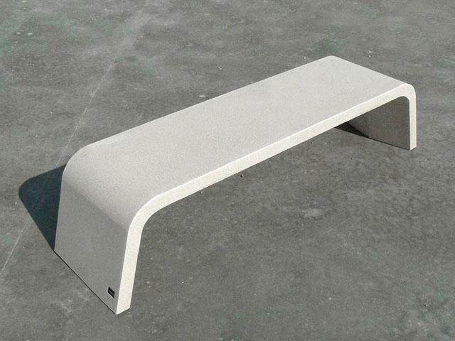 Бетонная скамейка с современным дизайном и плавными линиями.